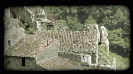 reclaim : High-angle footage looking down on the overgrown ruins of a large, simple stone building. Vintage stylized video clip.