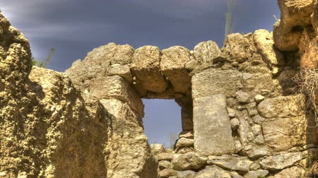 roofless : Low-angle time lapse of the roofless stone walls and door of a ruin. Panning shot.