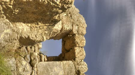 roofless : Low-angle time lapse of the roofless stone walls and door of a ruin. Vertical shot. Stock Footage
