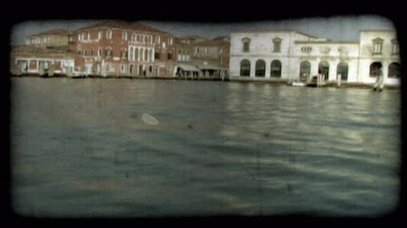 minério : Pan of scenery from a boat along an Italian river. Vintage stylized video clip.