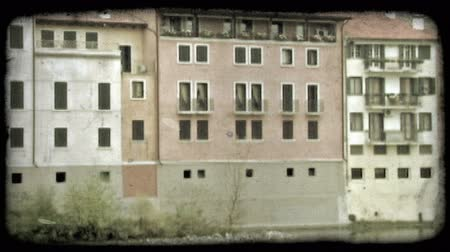 minério : Pan left shot of houses along the side of a river in Italy. Vintage stylized video clip.