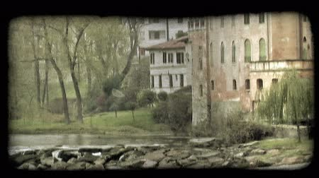minério : Shot of houses along the side of a river in Italy. Vintage stylized video clip.