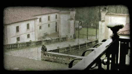 minério : Shot of the front gate of a house followed a pan right over the roof. Vintage stylized video clip.