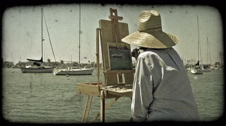 criar : Wide shot of female artist, dressed in a blue shirt and sun hat, as she carefully paints a rendition of the sea and anchored boats from the edge of an enclosed dock near Newport Beach in California. Vintage stylized video clip.