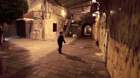 akko : Young Israeli Arab boy kicking around a soccer ball in an alley. At the end of the shot two men enter the frame and walk down the alley in Akko Israel. 02192011