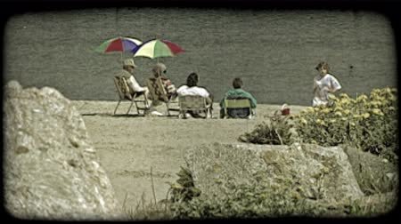 сбор винограда : Older couple sitting on beach chairs underneath colorful umbrellas on beach next to two women on beach chairs watch quiet lake front as girl wearing a tye dye shirt walkes toward flowers and large rock in foreground. Vintage stylized video clip. Стоковые видеозаписи