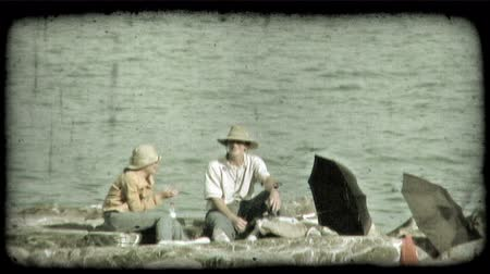 piknik : A couple enjoy a picnic on a rocky beach. Vintage stylized video clip. Stok Video