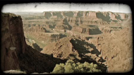 кустарник : Pan right to left of overlook on Dead Horse Point canyon in Utah detailing articulate red rock formations, the Green River, plateaus, dramatic shadows cast by sun, and colorful cliffs of the area. Vintage stylized video clip. Стоковые видеозаписи