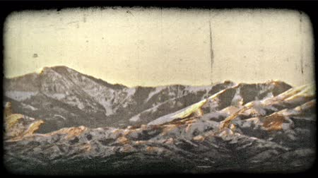 bronz : Pan of picturesque snow-capped mountain range softly lit by golden-bronze sunset at dusk. Vintage stylized video clip.
