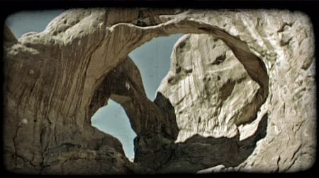 fenomen : Slow wide pan of two connected archs as they stretch above red rocks against a clear blue sky. Vintage stylized video clip. Stok Video