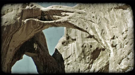 fenomen : Slow medium pan, right to left, of two connected archs as they stretch above red rocks against a clear blue sky. Vintage stylized video clip.