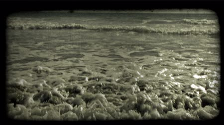 lét : Small waves, carrying sea froth, come in as they cover the beach before being pulled backward again by sea current as sailboat sails along in far distant background. Vintage stylized video clip.