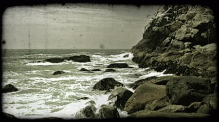 pacífico : Frowthy waves crash against large mossy rocks on the side of an island next to the pacific ocean. Vintage stylized video clip.