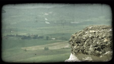 tahıllar : Close up shot of an interesting rock with a wide landscape of Italy in the background. Vintage stylized video clip.