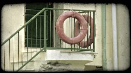 zábradlí : Two red lifesaver rings hanging on the stair rail of an Italian doorstep. Vintage stylized video clip.