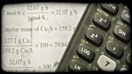 régi : Close-up pan of graphing calculator laying on math textbook. Vintage stylized video clip. Stock mozgókép