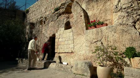 могила : Two tourists, a man and a woman, going into the Garden Tomb in Jerusalem, Israel, one of the speculated tombs where Jesus was buried.