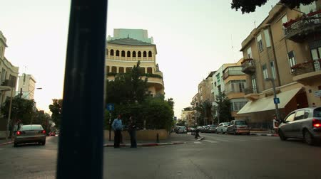 tiro : Dolly shot past a Tel Aviv city light pole of an intersection. Two Israelis are talking and standing as scooters and cars drive by. The shot is interesting because of the location; the street divides into two streets around a yellow building at this inter Stock Footage