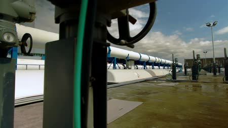 rurociąg : Dolly slider move up past valves and gauges on the roof of the IDE Ashkelon desalination plant in Israel, revealing the large pipes behind. Nice blue sky with fluffy clouds.