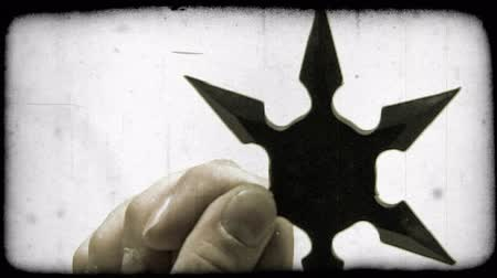 каратэ : Close-up shot of a shuriken in a persons hand. Vintage stylized video clip. Стоковые видеозаписи