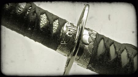 samuraj : Close-up shot of a katana sword being pulled out of its sheath. Vintage stylized video clip.