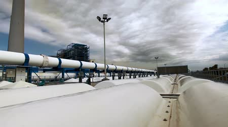 rurociąg : Slider dollyright to left on the roof of one of the buildings at the IDE Ashkelon desalination plant in Israel. The shot moves across the domes in the roof with a big white water pipe in the left side of the frame along with a huge smokestack. The clouds