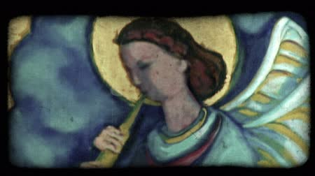 dolgok : Shot of a painting of an angel playing a flute-like instrument in Italy. Vintage stylized video clip.