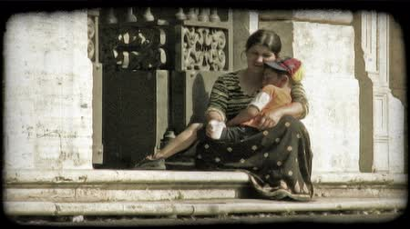 pažba : A homeless woman holds her son as they sit in poverty on the city steps. Vintage stylized video clip.