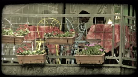 eatery : A shot of chairs, tables and flowers on the patio of an Italian cafe. Vintage stylized video clip. Stock Footage