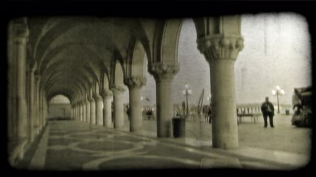 tahıllar : People walk through a walkway under some arches and through a plaza in Italy. Vintage stylized video clip.