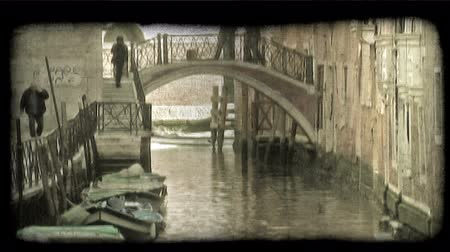 tahıllar : People walk on a bridge over a canal in Venice. Vintage stylized video clip. Stok Video