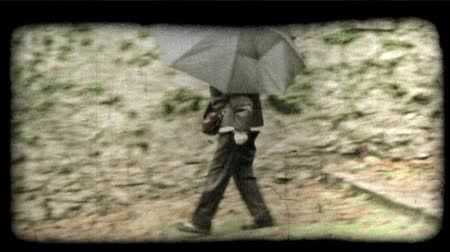 deszcz : A woman walks in the rain underneath an umbrella. Vintage stylized video clip. Wideo