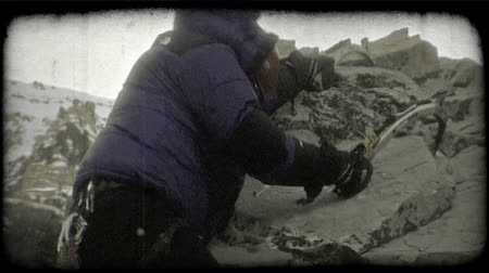 magasság : Mountain climber wearing a blue winter coat and professional winter climbing gear uses axes in both hands to pull himself around a threatening grey rock at the tip of a mountain peak. Vintage stylized video clip.