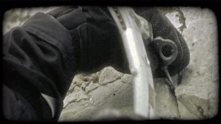 fenda : Mountain climber, wearing thick black gloves, hammers a metal stake into a rock crevice with a metal hammer. Vintage stylized video clip.