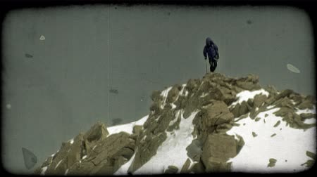 picos : Wide shot of mountain climber, wearing professional winter climbing gear and using hiking pole, reaching the top of a snowy, rocky bank at the peak of a high mountain where he stops to look over the mountainous terrain he has conquered. Vintage stylized v