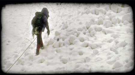 télen : Medium shot of mountain climber, wearing professional winter climbing gear and using hiking pole, as he climbs up snowy bank on shaded side of high mountain with a hiking rope trailing him. Vintage stylized video clip. Stock mozgókép