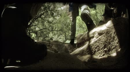 aventura : Low angle shot of man and womans boots as they hike through Zions red rock canyons with trees and mountains in the background. Vintage stylized video clip.
