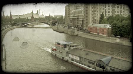 irrigate : Long Russian boatliner moves along deep canal that separates parts of Moscow, Russia with famous buildings and overcast sky in background. Vintage stylized video clip.