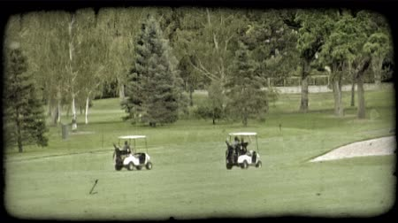 golf sahası : Two golf carts, one with two people and one with one person, follow each other along cart trail in  green golf course lined with various types of trees and containing sand pit to the right. Vintage stylized video clip.