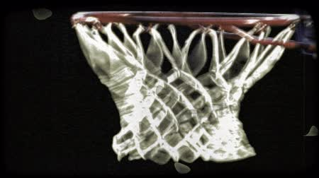 executar : Close-up shot of a Caucasian basketball player slam dunking the ball in slow motion. Vintage stylized video clip. Stock Footage