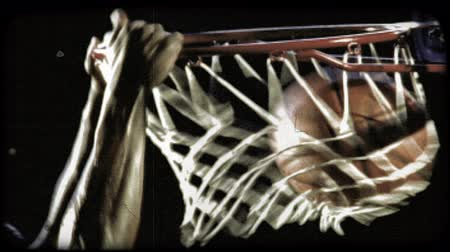 marmeláda : Close-up of an African-American basketball player slam dunking the ball in slow motion. Vintage stylized video clip.