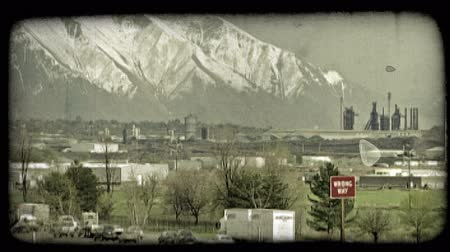пригород : Busy city highways running parallel to each other in foreground with power plant factory with smokestacks, valley city and tall, snow-covered Wasatch Mountains  rising high in background. Vintage stylized video clip.