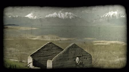 спокойные сцены : Time lapse medium shot of quiet highland scene with abandoned, old brick house frame on grassy hill in foreground and brown grasses next to large lake in background, with tall, grand, snow-covered Wasatch mountains rising up in far background behind lake, Стоковые видеозаписи