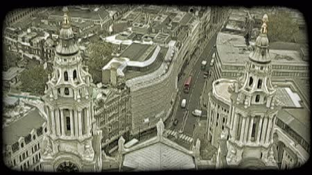 europa : Overlook from high viewpoint down to two spires of a church or municipal building with ornately designed architecture and streets below tall building-lined passages and intersections. Vintage stylized video clip. Wideo