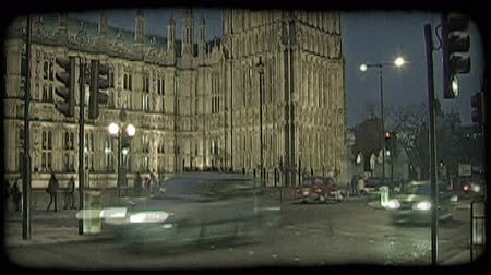 парламент : Time-lapse of English double decker buses, cars, and people crossing the lit street adjoining the English Parliament in London, England at dusk. Vintage stylized video clip.