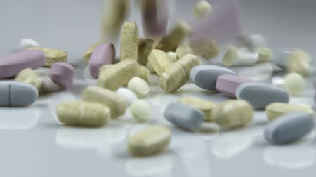 nutritional supplement : Supplement pills dropping into a pile.