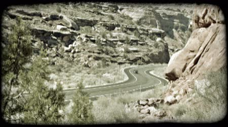 osamělost : Wide shot of dark green convertible as it drives slickly over a two-laned curved road in rocky desert, with red rock cliffs in background. Vintage stylized video clip.