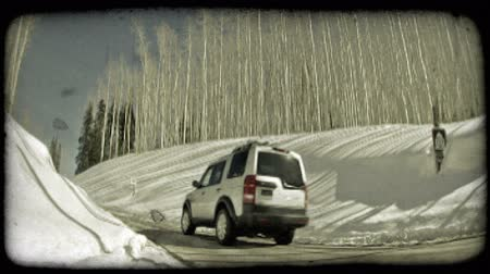 hluboký : Wide angle shot of whitesilver SUV as it drives up a hill, surounded on both sides by deep snow banks and bare, tall trees. Vintage stylized video clip.