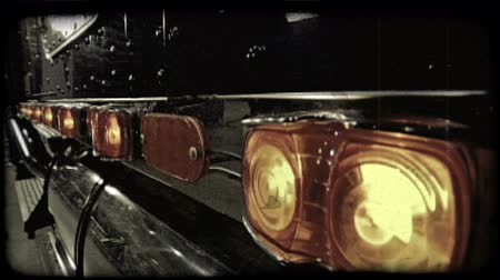 reflektor : Long row of truck side lights, which are on, and reflectors above metal parts of truck and below blue exterior of truck head. Vintage stylized video clip. Stock mozgókép
