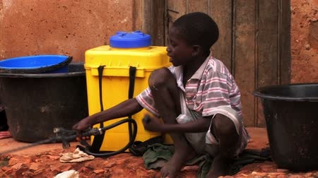 charakteristický : A young boy in Ghana sits pumping water from a container happily. Dostupné videozáznamy